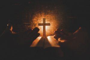 seseorang-membuka-kedua-telapak-tangannya-di-atas-kitab-dan-di-depan-salib-Isa-memohon-ketenangan-hati