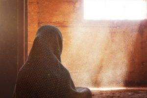 seorang-wanita-muslim-sedang-memandang-jendela-yang-diterangi-cahaya-matahari