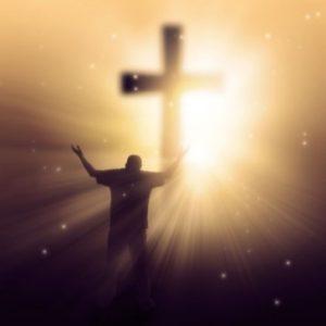 seorang-pria-mengangkat-kedua-tangannya-di-hadapan-salib-Isa-yang-diterangi-cahaya